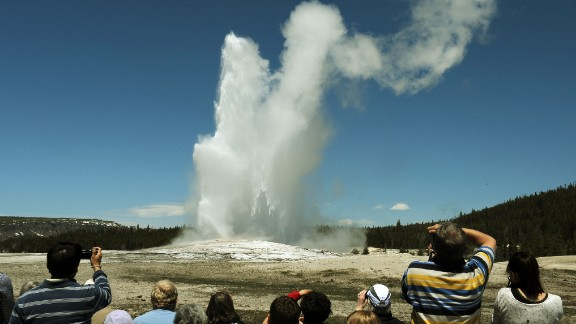 """Tourists watch the Old Faithful geyser in the Yellowstone National Park in Wyoming in June 2011. One tourist told a Massachusetts newspaper that National Park Service guards treated members of her tour group brusquely and told them not to """"recreate"""" while taking pictures of bison."""