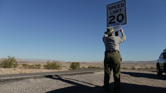 Park maintenance worker Donna Curry tapes up a sign on October 1 notifying visitors the picnic facility in Lake Mead National Recreation Area near Boulder City, Nevada, is closed. A Nevada couple told CNN affiliate KTNV-TV they were kicked out of their cabin, which is on federal land.