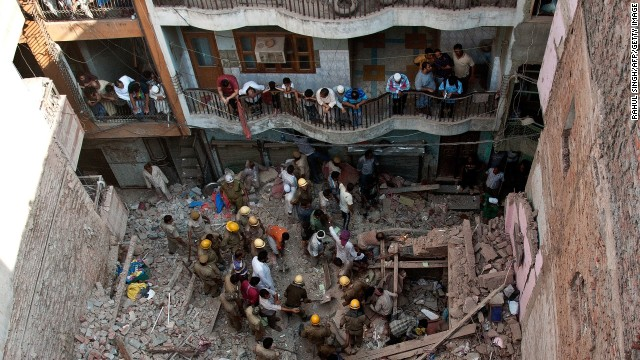 Indian rescue workers search for victims from the rubble of a collapsed building in New Delhi on October 9, 2013.