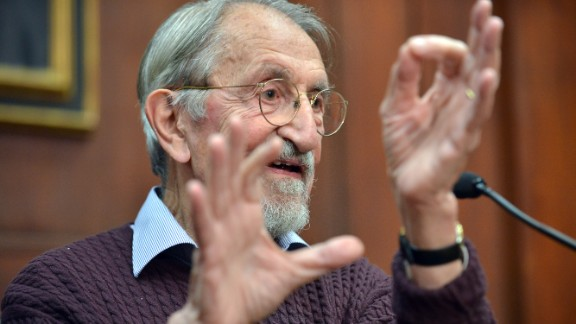 Martin Karplus describes molecular behavior as he speaks to reporters at Harvard University in Cambridge, Massachusetts, after being awarded the Nobel Prize in chemistry on October 9.  The three men