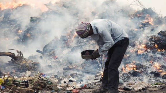 A migrant worker scavenges for materials in a landfill in the Maldives. Thilafushi is an artificial island created by filling one of the Maldives