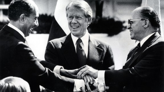 President Jimmy Carter, center, Egyptian President Anwar Sadat, left, and Israeli Prime Minister Menachem Begin join hands after signing the Camp David Accords. Sadat and Begin won the Nobel Peace Prize in 1978.