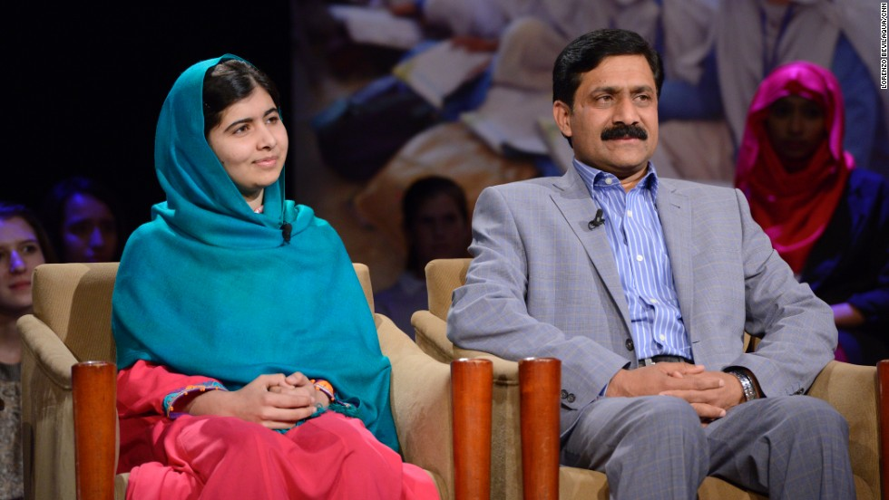 Malala sits onstage with her father Ziauddin Yousafzai.