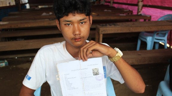 Zaw Min Paing poses with his army documentation. He was recruited at the age of 15 and spent more than four months in a training center before being released to his parents. He
