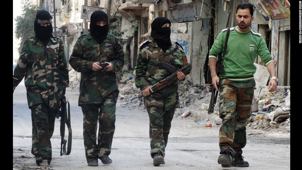 Masked female rebel fighters walk alongside their trainer on a street in the Salaheddin district of Aleppo, Syria, on October 8.