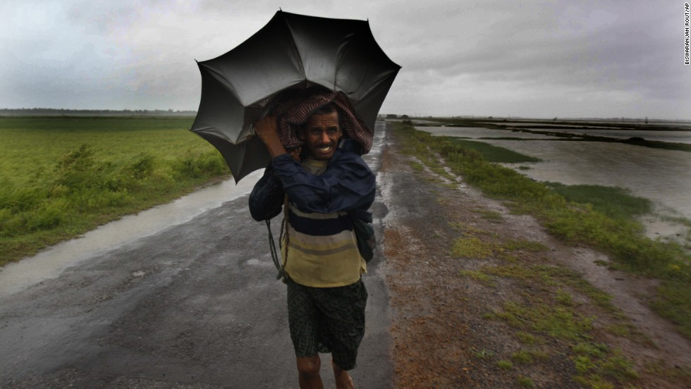 An Indian villager braves the strong winds and rain as he walks to safety in the village of Podampeta on October 12.
