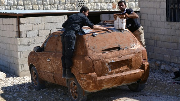 Rebel fighters cover a car in mud for camouflage at an undisclosed location in Syria
