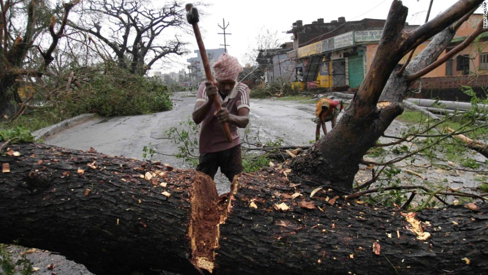 A municipal worker cuts a tree uprooted by the cyclone to clear a main highway in Berhampur, India, on October 13.