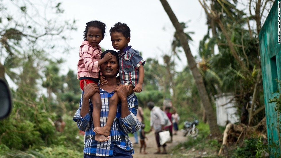 A man carries his children in Sonupur on October 13.