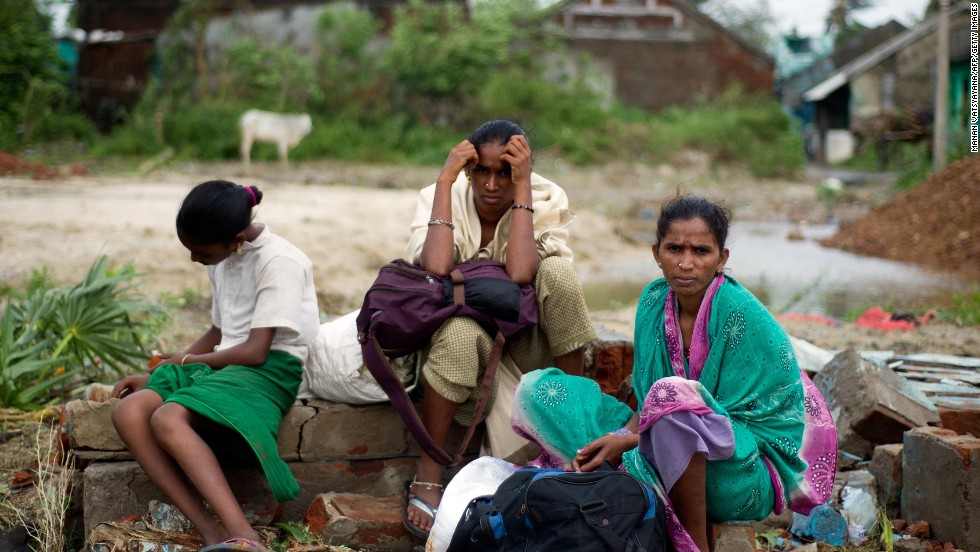 A displaced family waits at the village of Sonupur, India, on October 13.