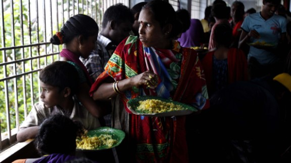 Evacuated villagers watch the strong winds and rain as they eat a meal in a temporary cyclone shelter in the town of Chatrapur, India, on October 12.