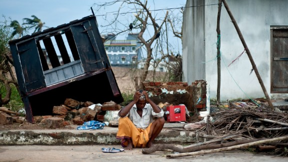 Bhagwan, a coconut seller, sits in front of his destroyed shop in the town of Gopalpur on Sunday, October 13.