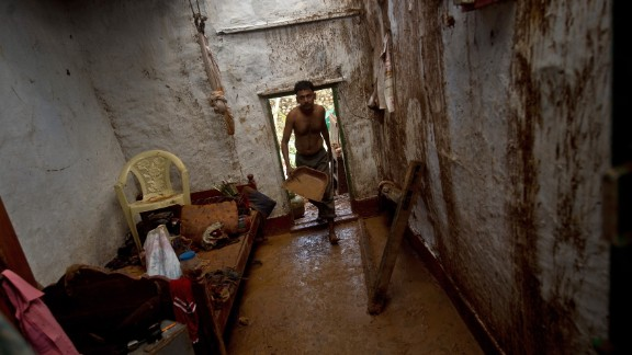 Janardan cleans his house of mud after overnight rains at the fishermen