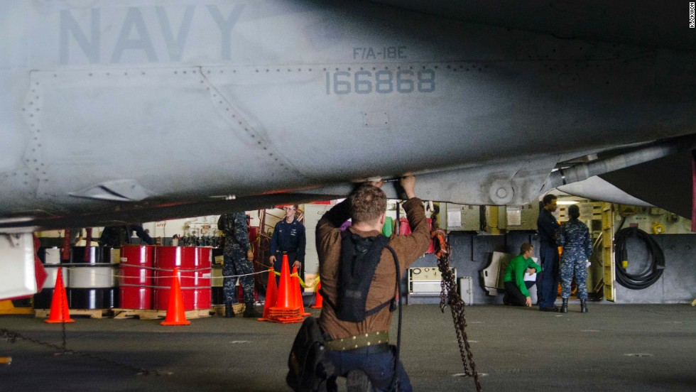 Aircraft carrier crew works on the fuselage of an F/A 18-E Super Hornet. According to the U.S. Navy, there are more than 500 of the aircraft in operation throughout the fleet.