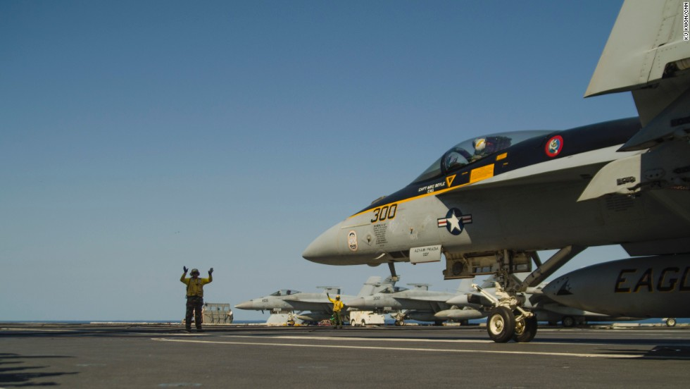 Landing Signal Officer guides in a fighter jet on the deck of the USS George Washington. The Naval Institute categorizes the Nimitz-class ship as a 'super carrier.'
