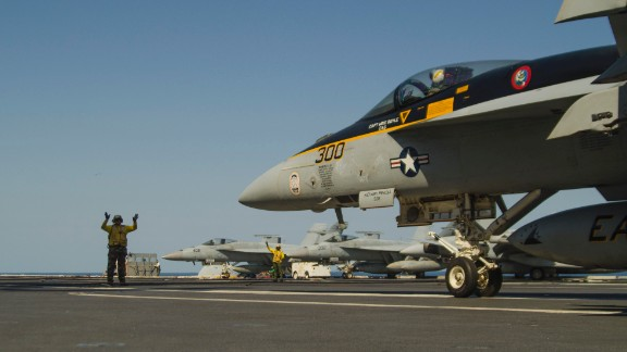 Landing Signal Officer guides in a fighter jet on the deck of the USS George Washington. The Naval Institute categorizes the Nimitz-class ship as a