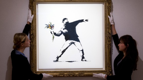 "Gallery assistants adjust Banksy's ""Love Is in the Air"" ahead of an auction in London in June 2013. The piece was sold for $248,776."