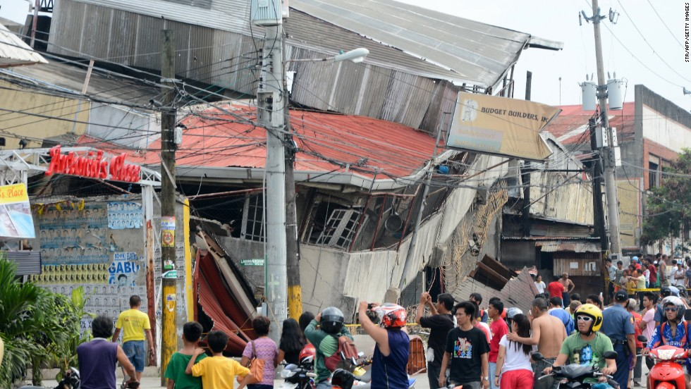 People gather outside damaged buildings in Cebu on October 15.