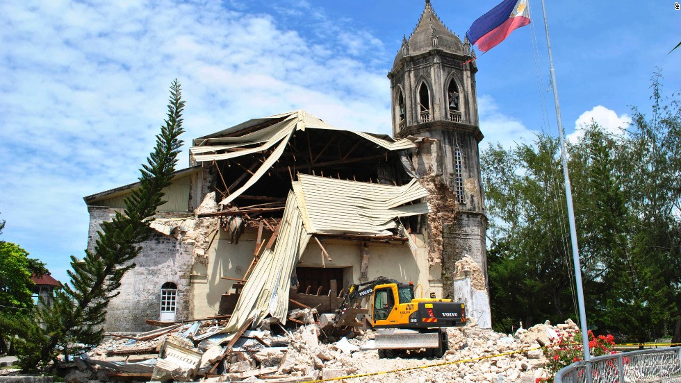 A crane sifts through the rubble of Our Lady of Assumption Parish Church in Dauis on October 15.