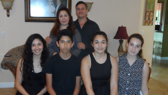 After their father was deported, Cesia Soza, bottom left, and her brother Ronald Jr. have lived with the Sandigo family in Miami.