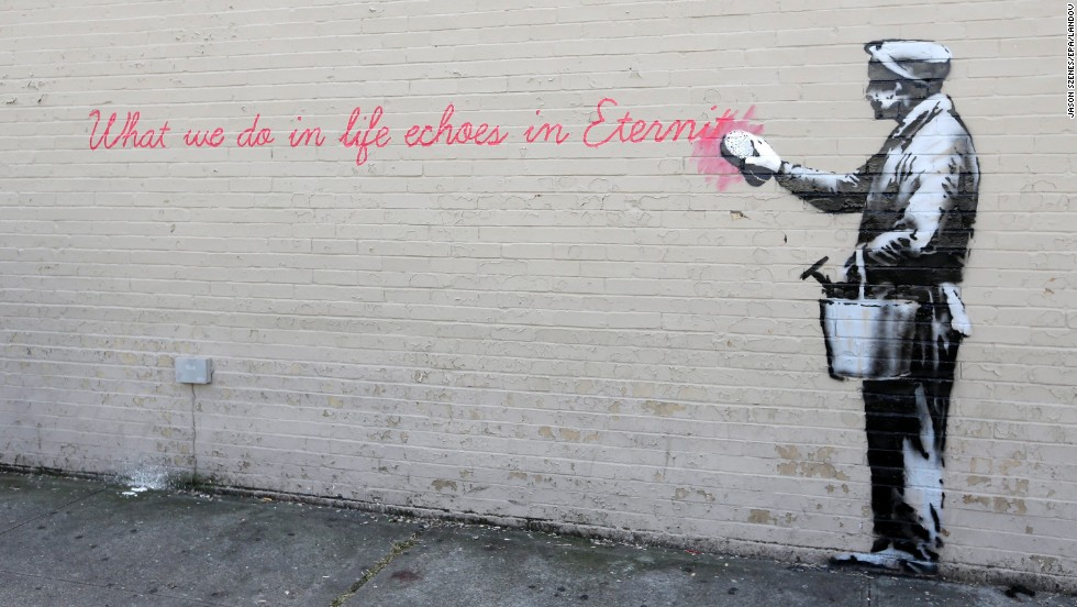 "A Banksy mural is seen on a wall in Queens. The quote is from the movie ""Gladiator."" It says, ""What we do in life echoes in eternity."""
