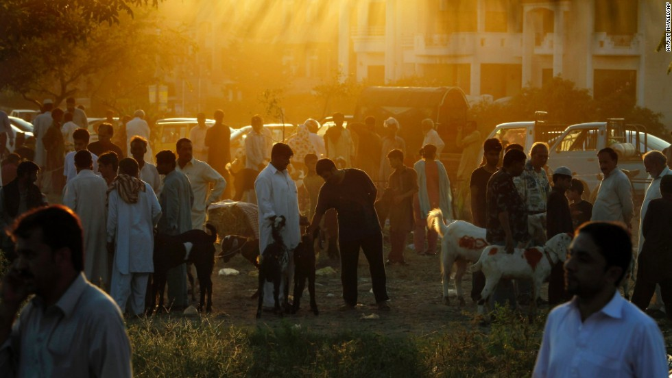 "People visit a small livestock market to buy sacrificial animals for the Muslim holiday of Eid al-Adha, or ""Feast of Sacrifice,"" in Islamabad, Pakistan, on Tuesday, October 15. Muslims traditionally sacrifice sheep, goats, cows and camels to commemorate the Prophet Abraham's readiness to sacrifice his son on God's command."