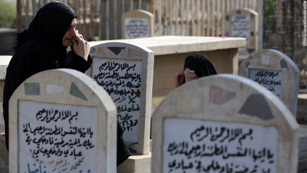 Iraqi women visit the grave of a loved one at a cemetery in Baghdad on October 15. Eid al-Adha began in Iraq with a bomb ripping through a crowd of worshippers as they left a Sunni mosque.