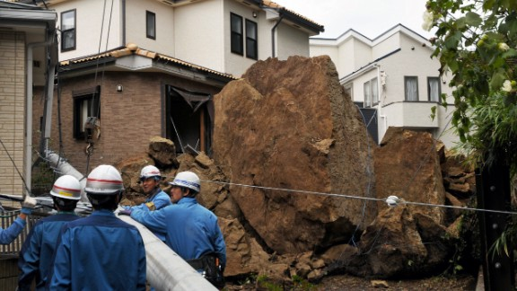 Rocks from a landslide down an electric pole outside a house in suburban Tokyo.