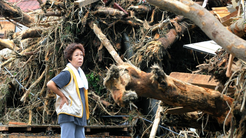A  woman looks at devastation caused by a landslide.