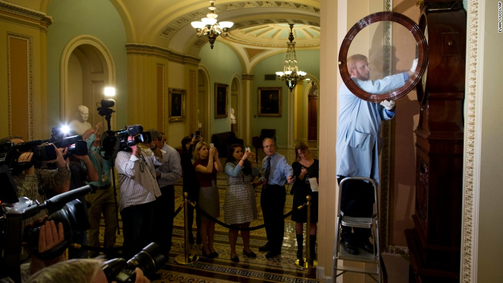 Museum specialist Richard Doerner winds the historic timepiece known as the Ohio Clock outside the Senate chamber on October 17. The clock stopped during the 16-day shutdown when federal workers were furloughed.
