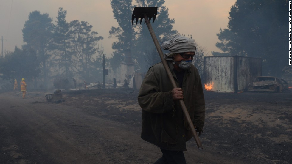 Sean Butler walks with his face covered after fighting fires with other residents of the historic township of Newnes Junction on October 17.