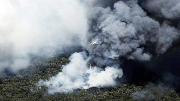 A helicopter works to extinguish bush fires burning near Winmalee on October 18.