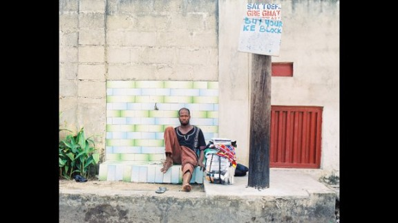 """""""Portrait of a Trader,"""" by Nigerian Emeka Okereke, shows a street trader taking a short break from his work among the heavy traffic of Lagos."""
