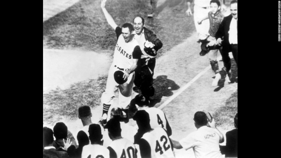 A jubilant Bill Mazeroski of the Pittsburgh Pirates walks across home plate to score the winning run of the World Series against the New York Yankees in 1960. Mazeroski is selling his old gear at an auction in November.