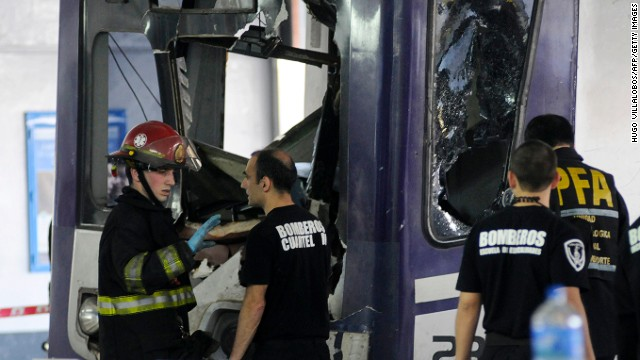 Firefighters inspect a commuter train that failed to stop and crashed at the end of the line at a railway terminal in Buenos Aires.