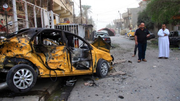 Civilians inspect the aftermath of a car bomb attack in Baghdad, Iraq, on Saturday. At least 350 people have been killed during the violence in Iraq in October.