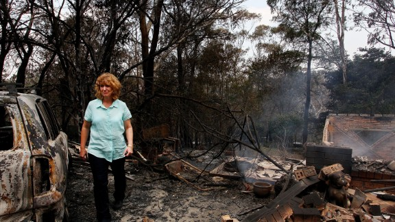 Leanne Brown inspects the remains of her home following severe bush fires on October 18, 2013 in Winmalee, Australia.