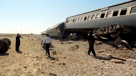 People survey the wreckage of a Jaffar Express train hit in three blasts near Naseerabad district in Pakistan