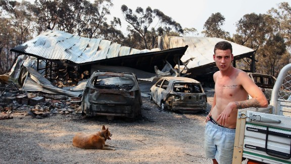 A man in Yellow Rock, Australia, stands in front of a building on Monday, October 21, that was destroyed by the bush fires scorching the country