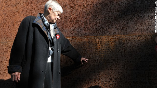 A woman points to the name of her killed relative at the Monument dedicated to Polish victims of the 1940 Katyn massacre.