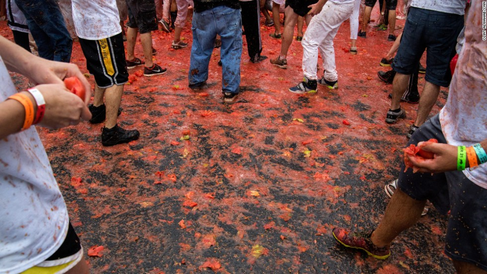 Participants slip and slide around the parking lot that was converted into the stage for the massive tomato fight.