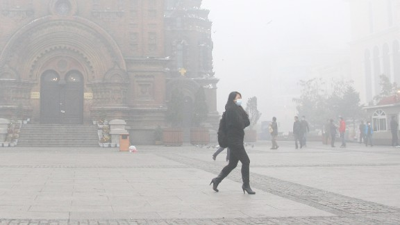 A woman wearing a mask walks along a road as smog engulfs Harbin, China, on Tuesday, October 22. Expressways, schools and an airport were closed after smog disrupted one of northeast China