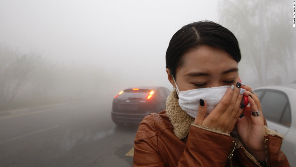 "A woman walks in the Harbin smog October 21. ""We can smell the smoke in the air,"" one man told CNN."