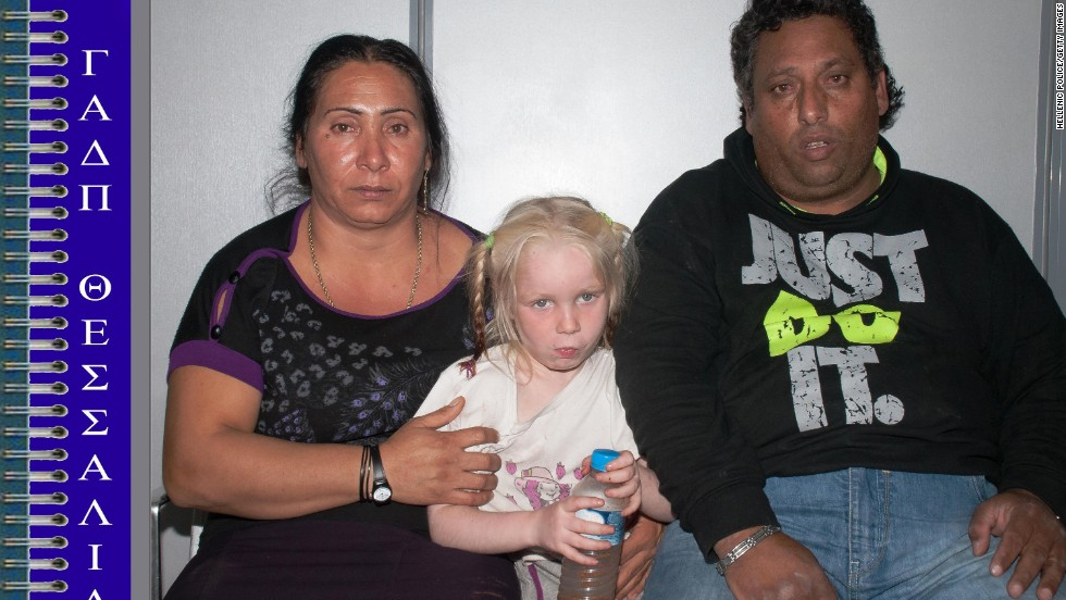 In this handout photo provided by police, suspects Eleftheria Dimopoulou, 40, and Christos Salis, 39, sit with the girl. A lawyer for the couple told the Reuters news agency that the couple adopted the girl with the permission of her biological mother.