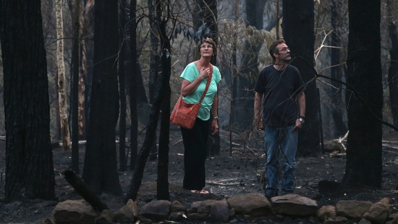 People walk around the area behind their destroyed home in Winmalee on October 22.
