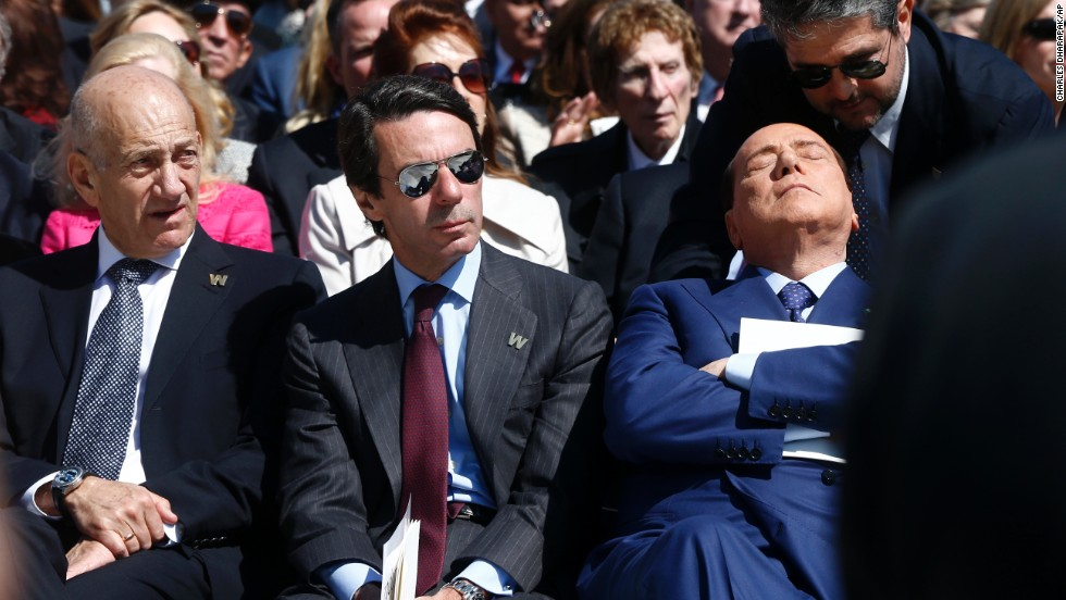 Berlusconi closes his eyes as he listens to a man speak in his ear at the dedication of the George W. Bush Presidential Library in Dallas on April 25.