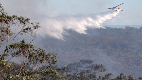 A helicopter drops water on fires burning in Faulconbridge on Thursday, October 24.
