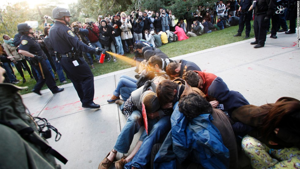 Police Lt. John Pike at the University of California, Davis, uses pepper spray to break up Occupy UC Davis protesters on the school's quad on November 18, 2011. This image sparked controversy amid the Occupy protests and fueled the flames for protesters. A judge ruled that the university must pay Pike $38,000 in workers' compensation for the depression and anxiety he suffered as a result of the backlash from the incident.