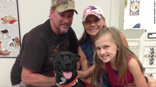 Andi Davis, center, rescued this gravely injured black and white pit bull while hiking in Arizona. Also pictured are her husband Jason, daughter Jessi. Elijah, the rescued dog, is recovering from bullet wounds.