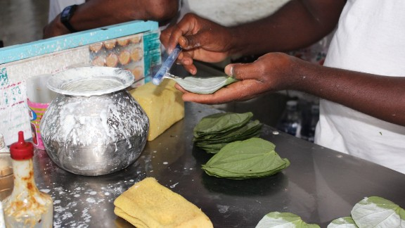 Kyaw Thet works quickly at his stall in central Yangon. He first coats the betel leaves in slaked lime before lining them up in rows on the counter to add the extra ingredients.